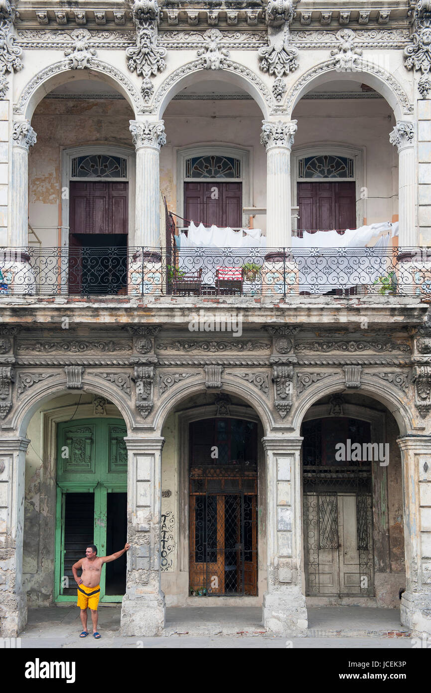 HAVANA - CIRCA JUNE, 2011: Cuban man stands between the arches of a dilapidated row of colonial buildings in a residential - Stock Image
