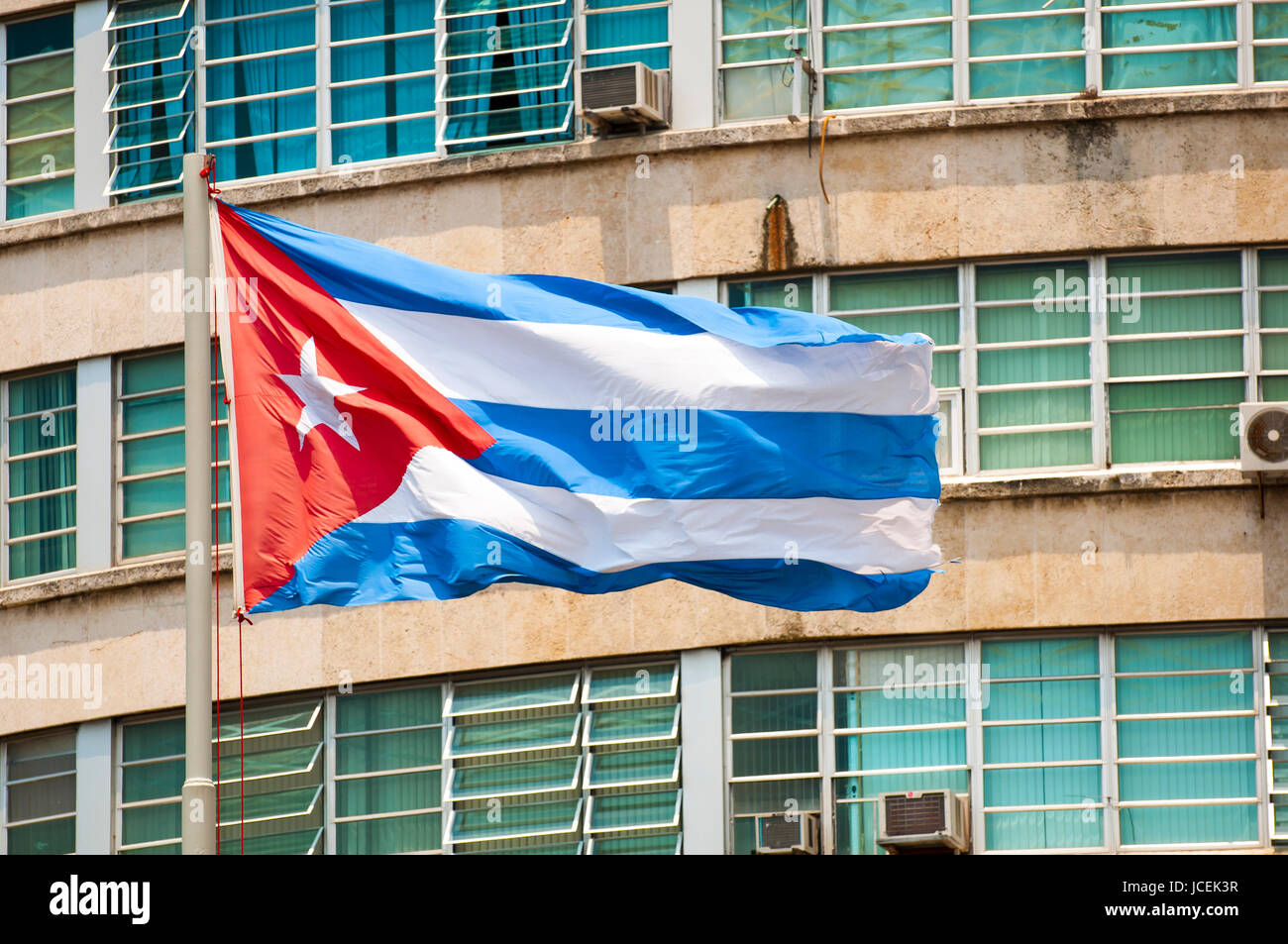 Cuban flag flying from a flagpole in the wind in front ministerial building at Revolution Plaza in Havana, Cuba - Stock Image