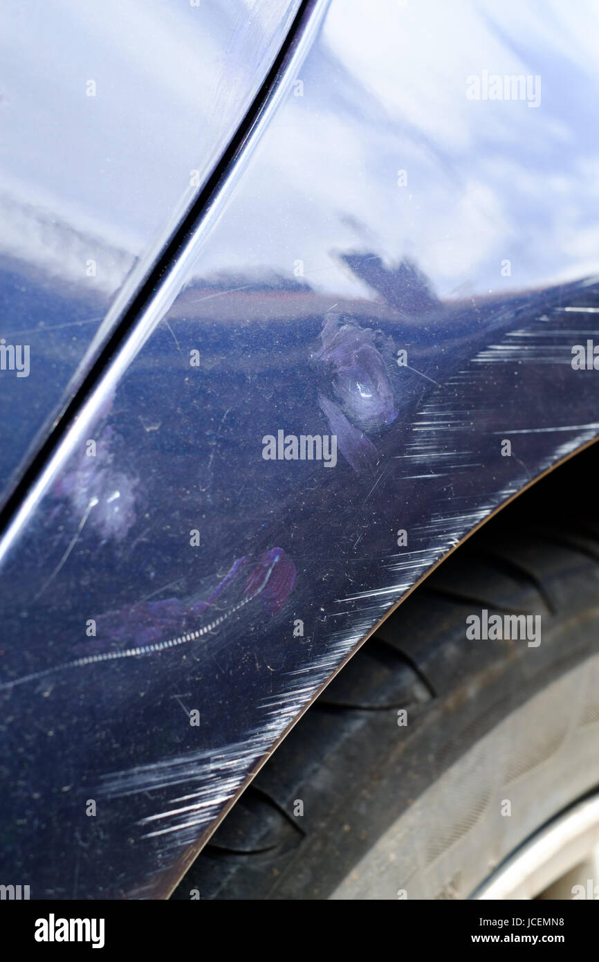 Scratches and minor dents on front wing of blue coloured road car. - Stock Image