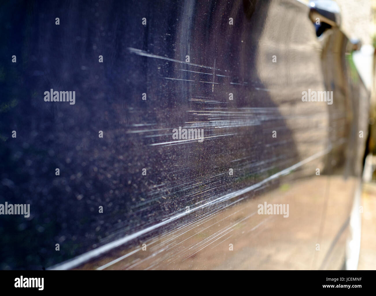 Scratches and minor dents on door panel of blue coloured road car. - Stock Image
