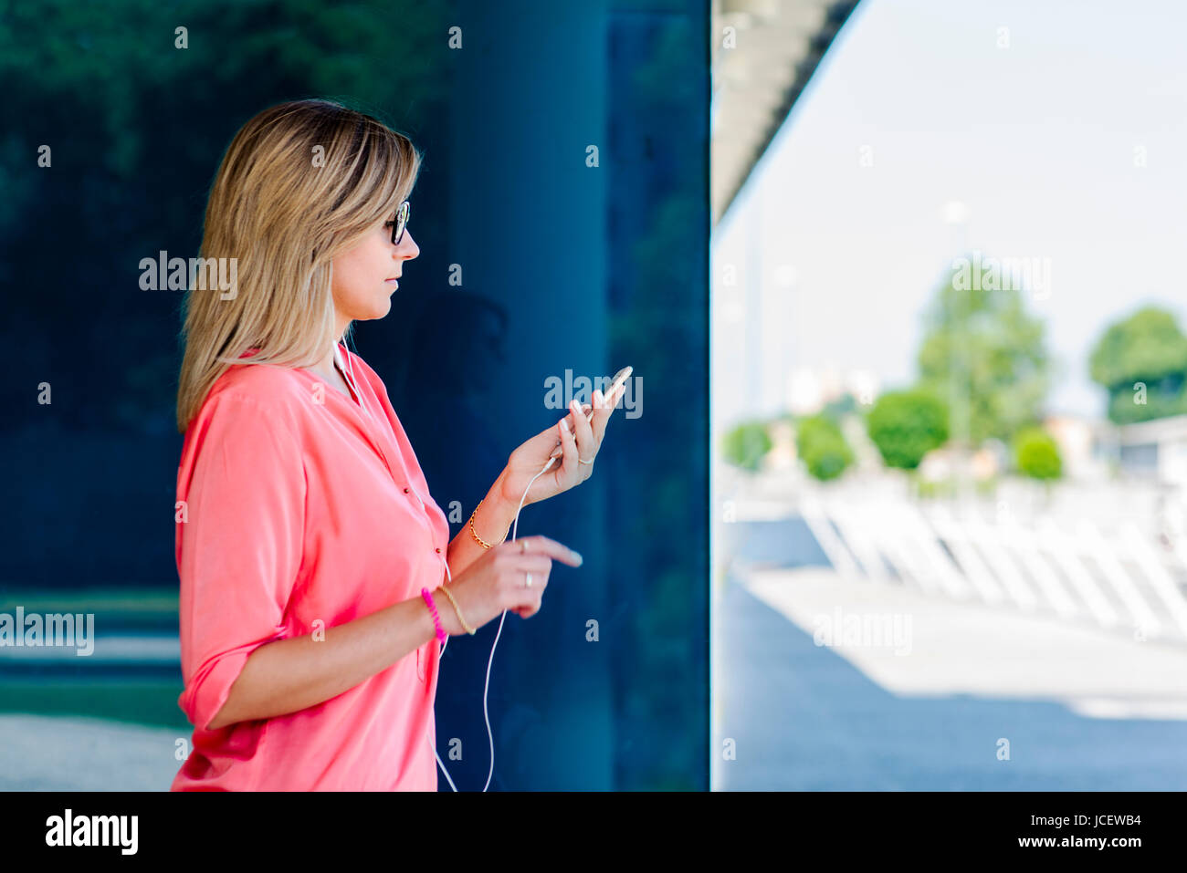 Portrait of a young confident caucasian  woman in a big city modern district with smart phones, earphones, connected, - Stock Image