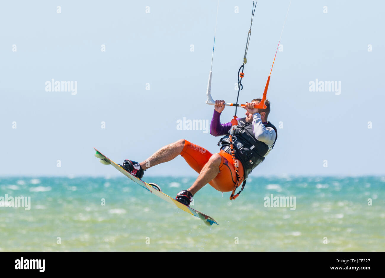 A man Kitesurfing at sea in Summer in the UK. - Stock Image