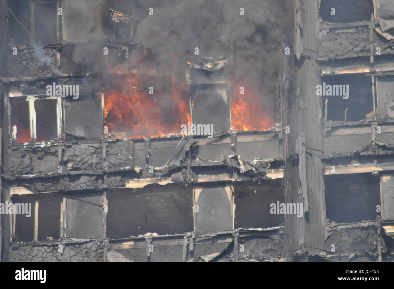 Flames still rage as firefighter continue to battle the Grenfell Tower blaze the following day as new crews from - Stock Image