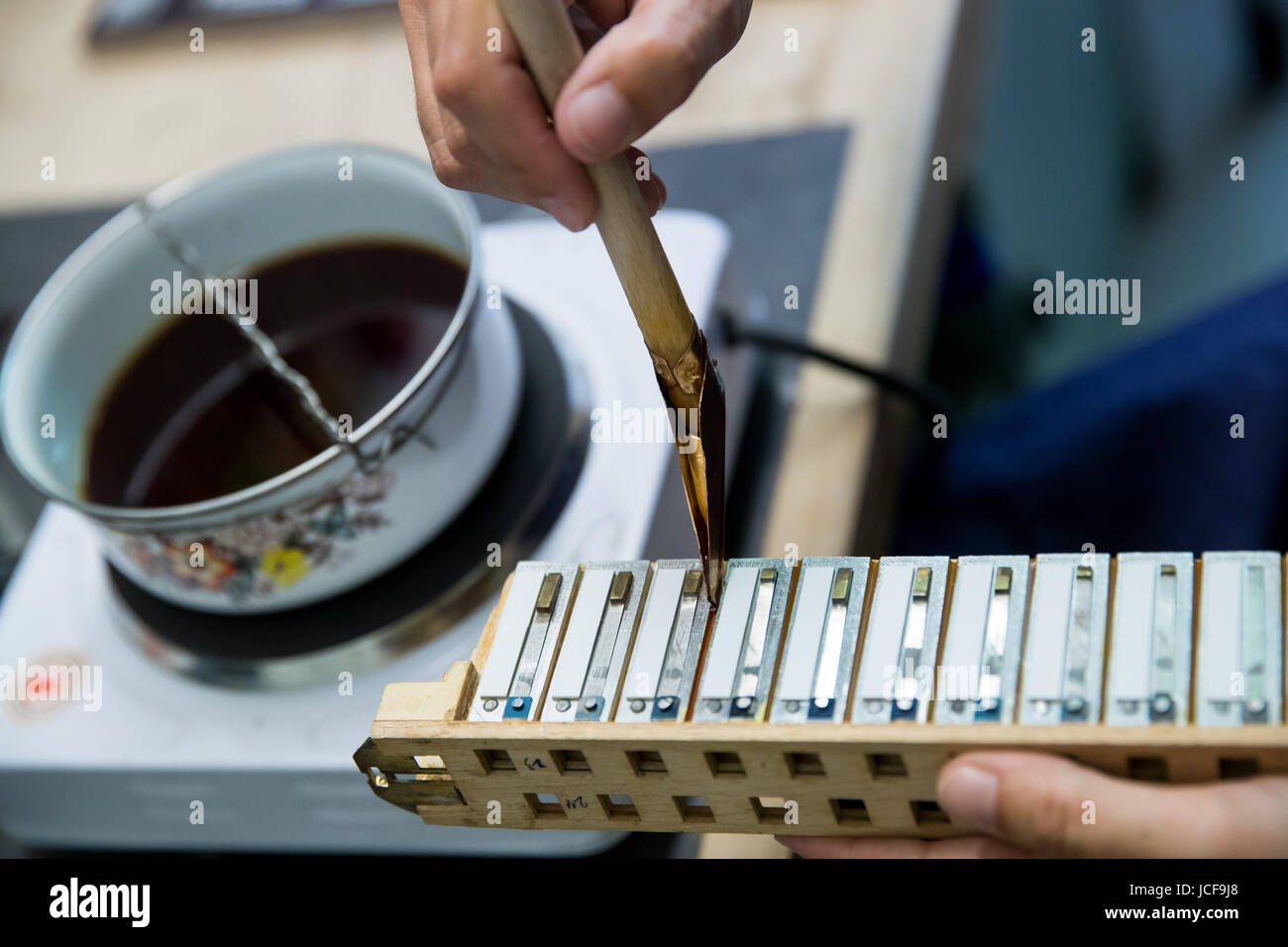 Nuremberg, Germany. 12th June, 2017. Simone Wiech, restorer of accordion instruments, waxes the valves of an accordion - Stock Image