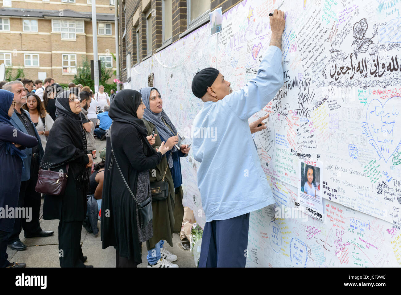 London, UK. 15th June, 2017. A man writes a message of condolence to the victims of the Grenfell Tower fire. The Stock Photo
