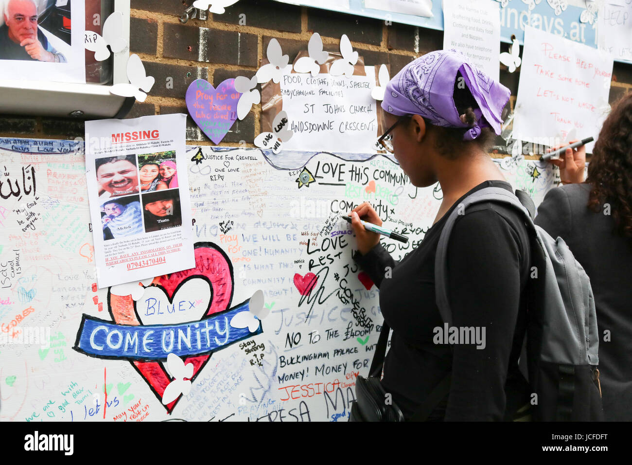 London, UK. 16th June, 2017. A woman pens messages of sympathy and condolences on the wall of the Latimer Community Stock Photo