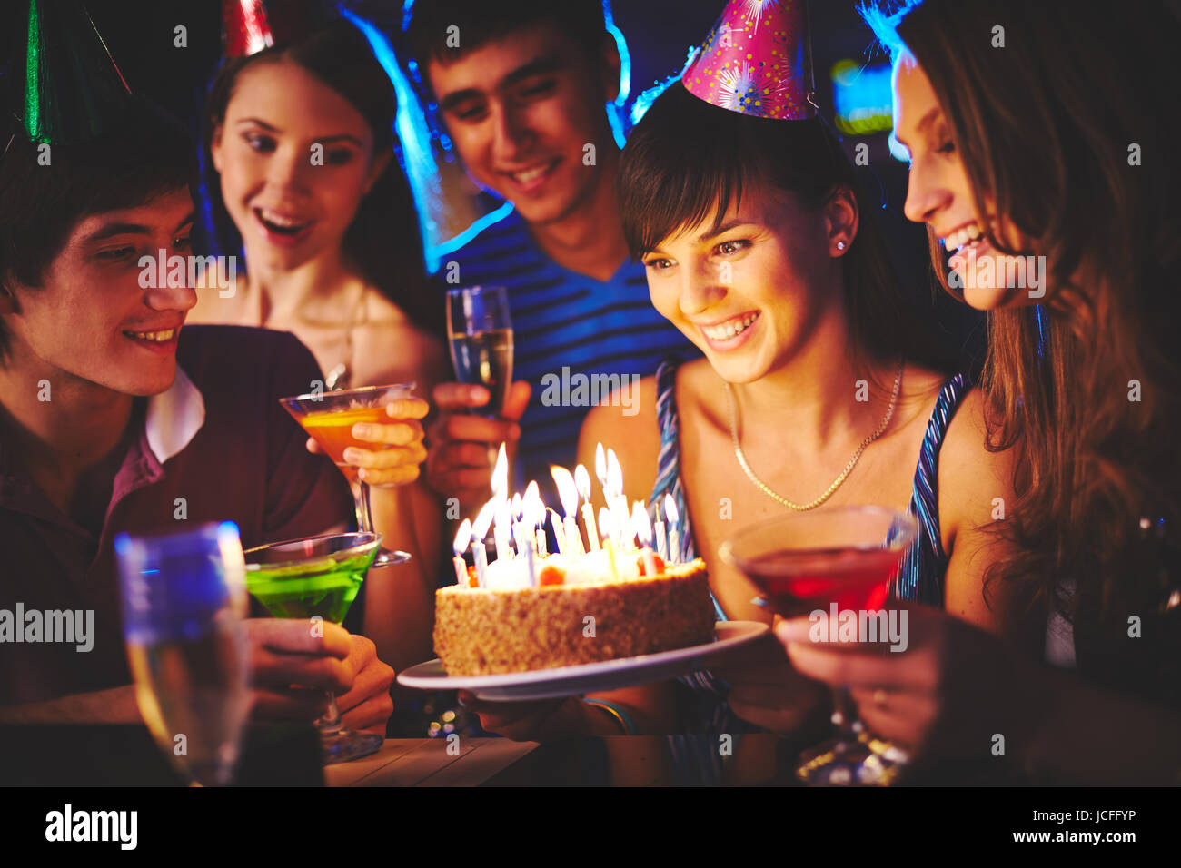 Charmed Girl Looking At Birthday Cake With Burning Candles At Party