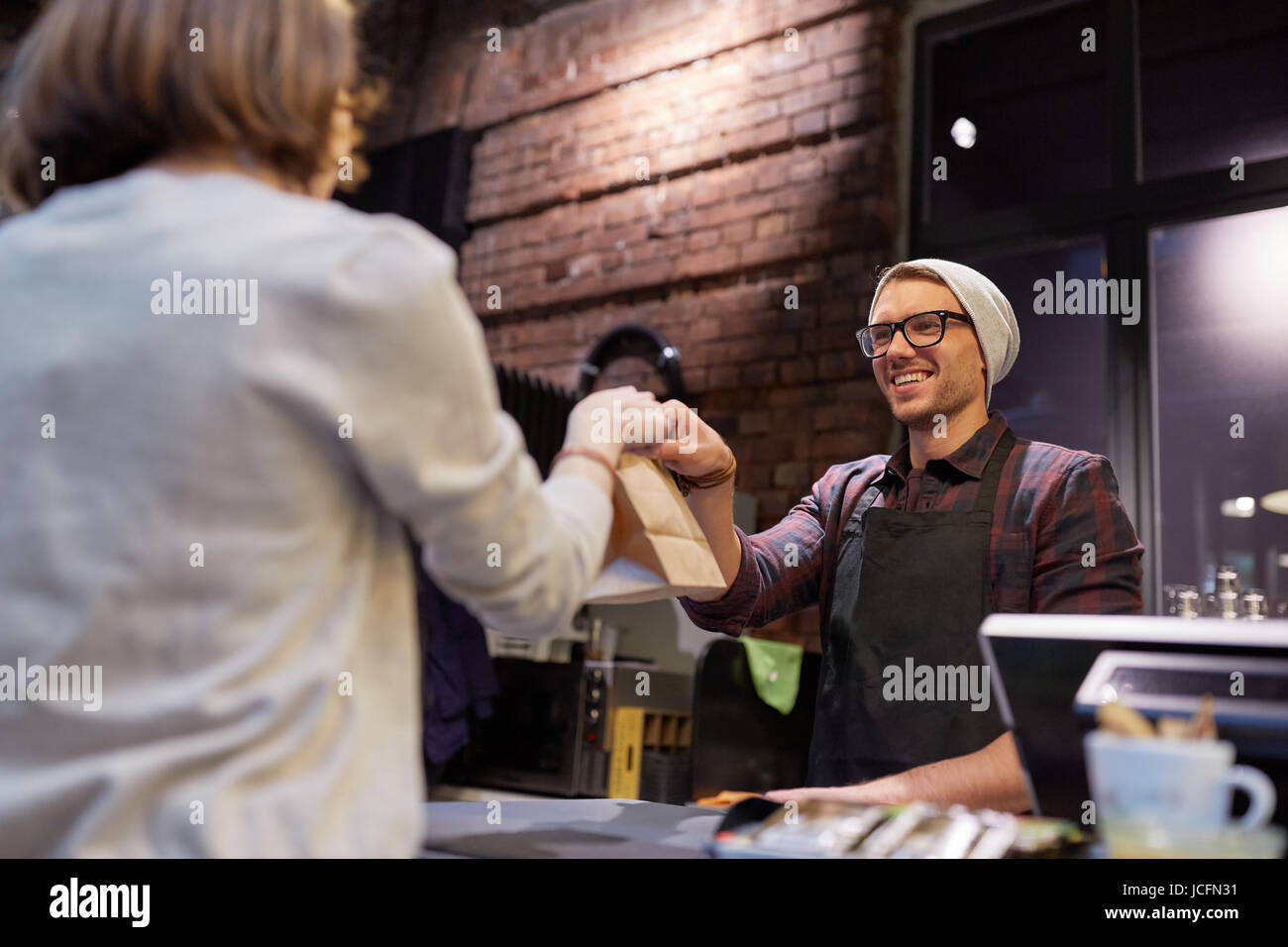 woman taking paper bag from seller at cafe - Stock Image