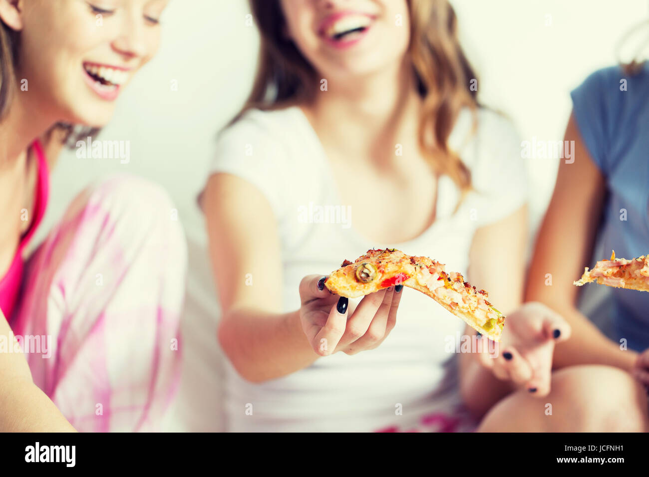happy friends or teen girls eating pizza at home Stock Photo