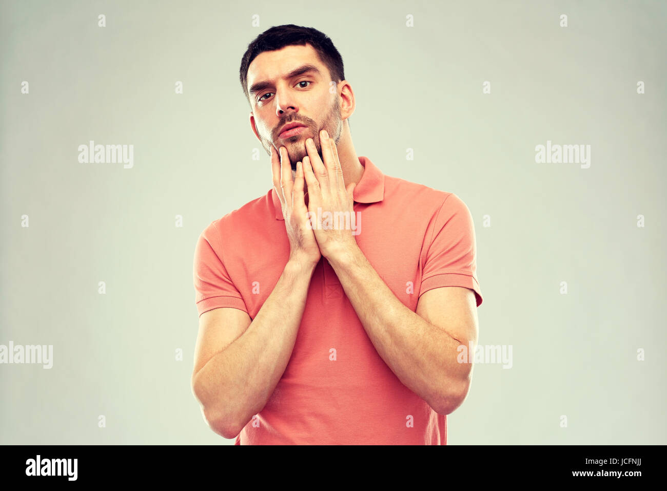 young man touching his face over gray background - Stock Image