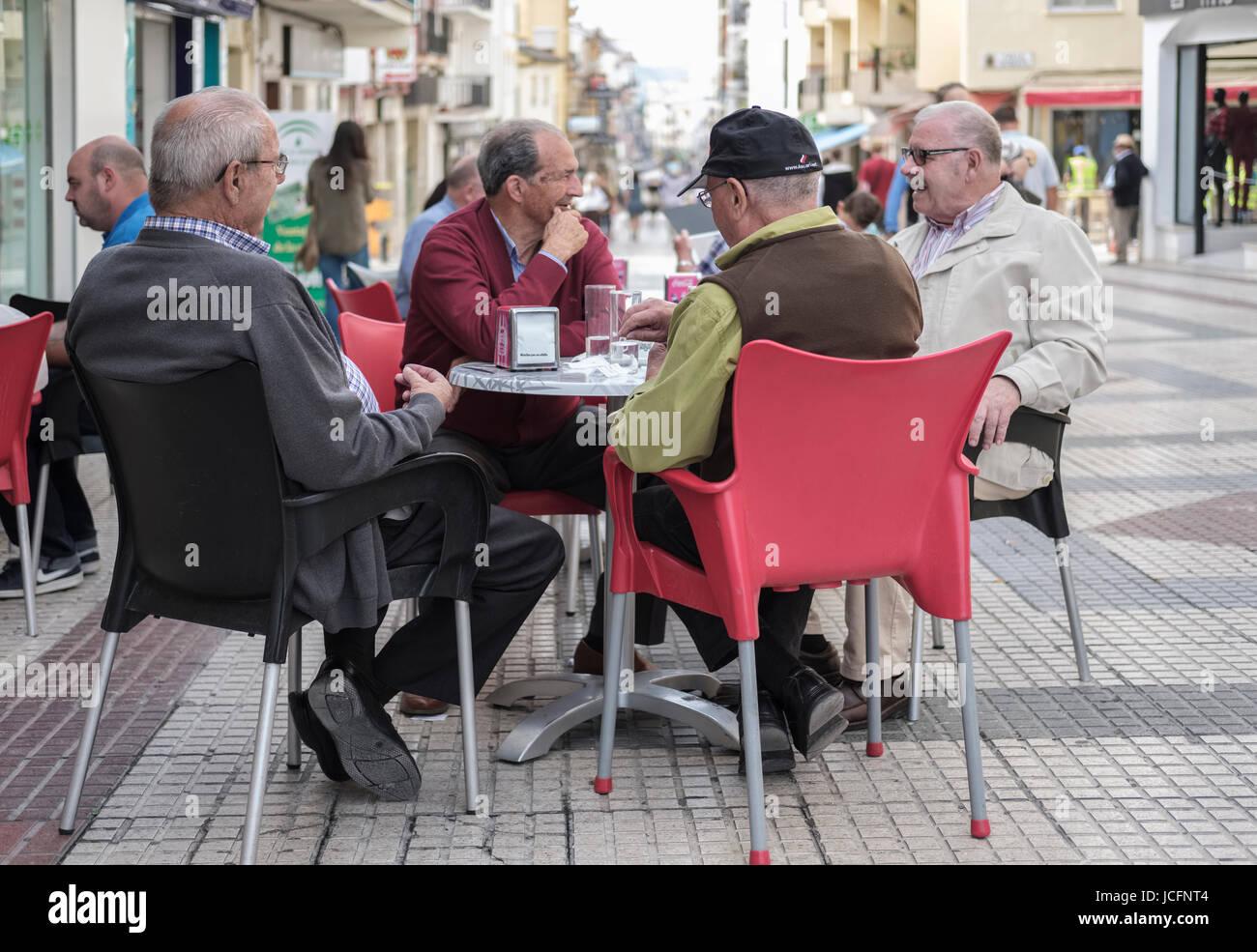 Four older men having morning drinks, Ronda, Málaga, Spain - Stock Image