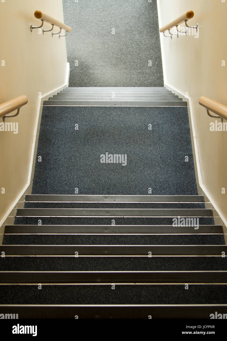 Stairway going down in office block with hand rails and  blue carpet tiles, no trip hazards and no safety gates - Stock Image