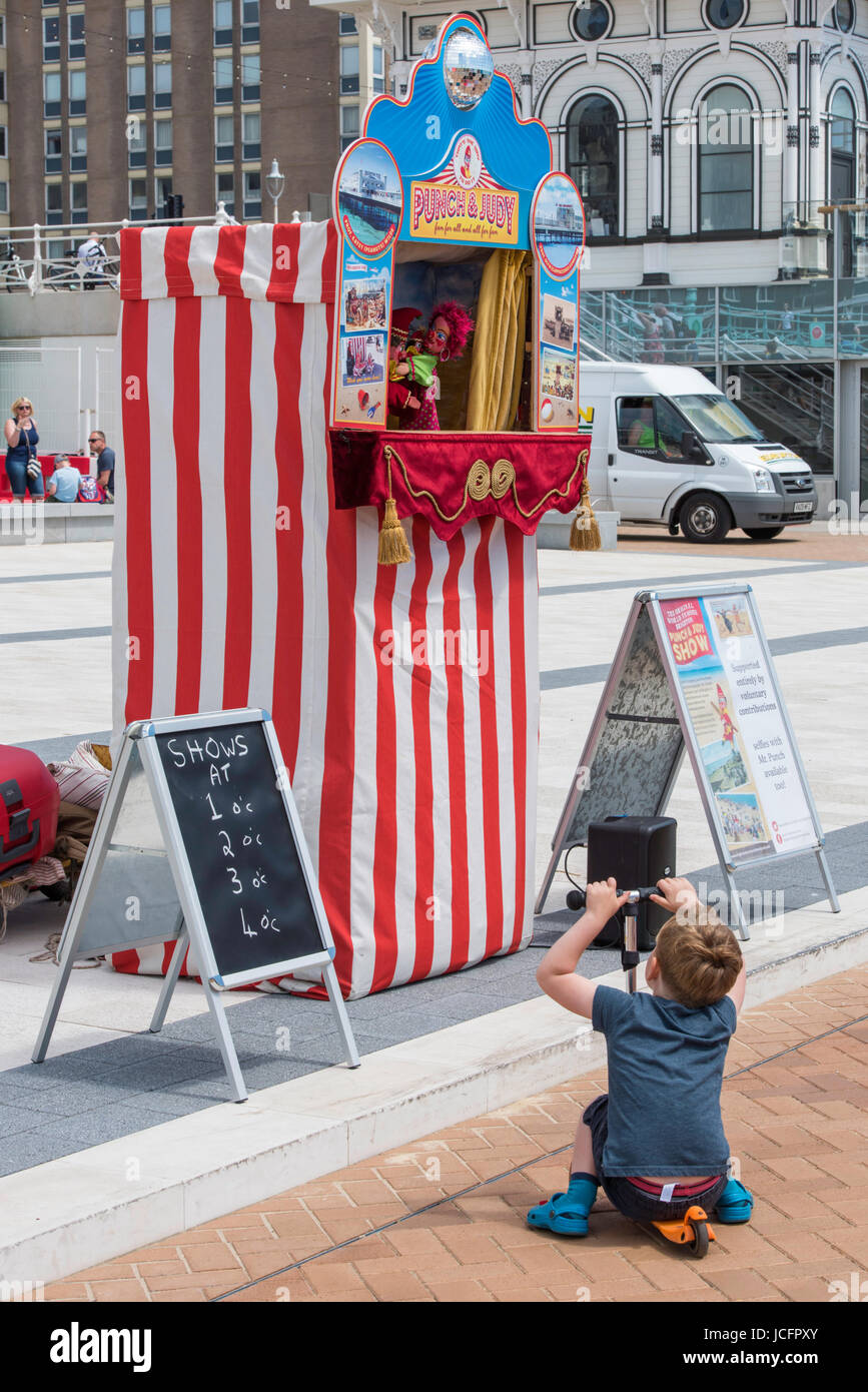 Punch and Judy show on Brighton seafront. A small boy on a scooter sitting and watching the performance. - Stock Image