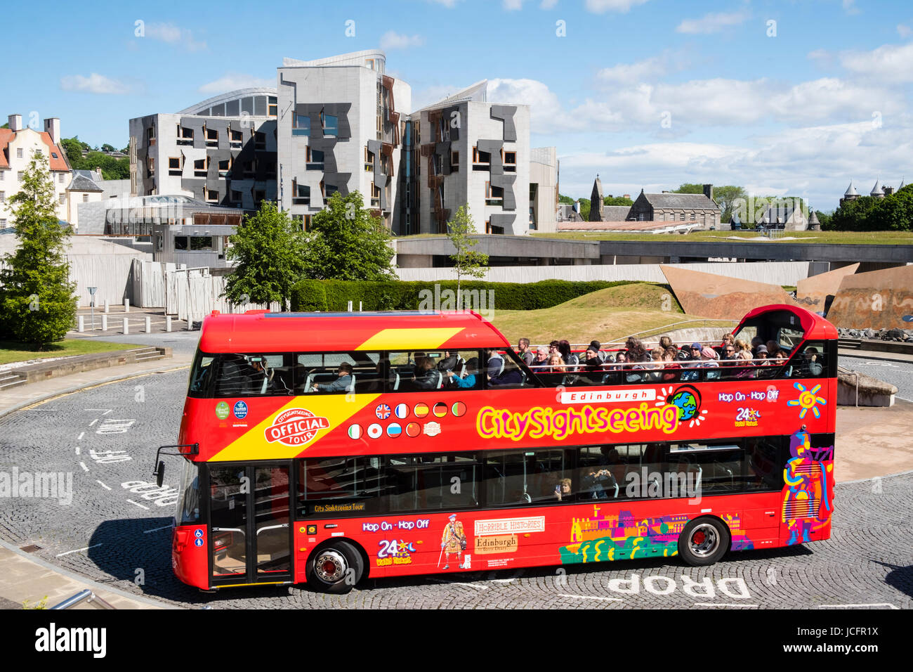Tourist bus outside the Scottish Parliament building at Holyrood in Edinburgh, Scotland, United Kingdom. - Stock Image