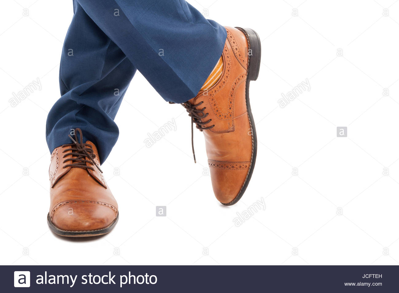 Closeup of stylish male with elegant shoes  posing with legs crossed in close-up view on white background - Stock Image