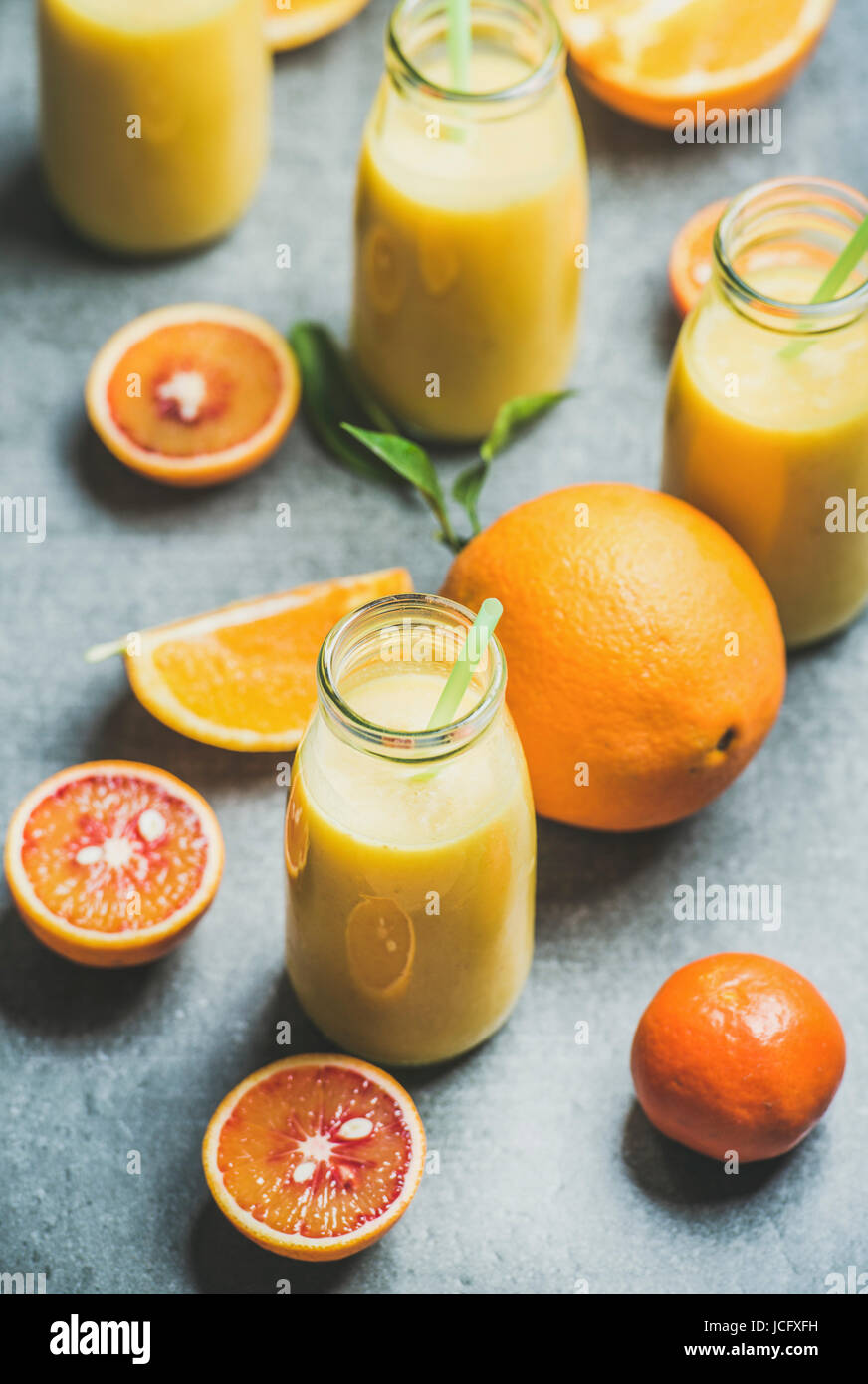 Healthy yellow smoothie with citrus fruit and ginger in bottle over grey concrete background, selective focus. Clean - Stock Image