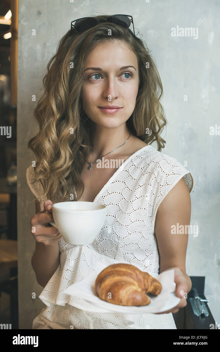 Blond curly haired young woman wearing white dress sitting in cafe with cup of cappuccino and croissant - Stock Image