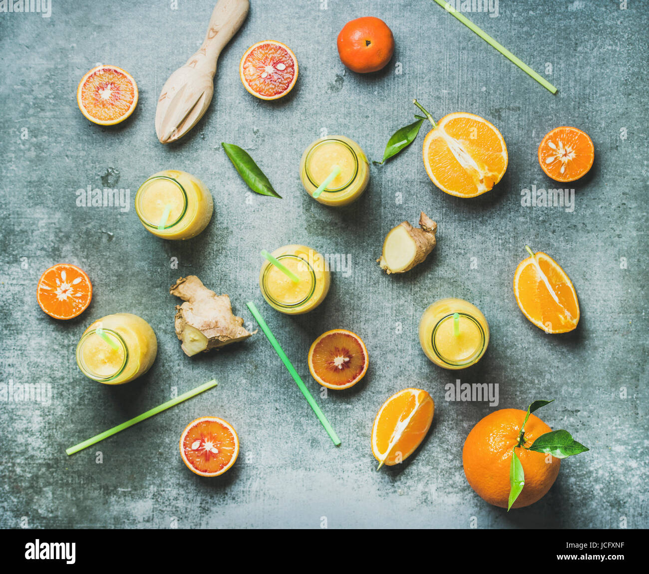 Healthy yellow smoothie with citrus fruit and ginger in bottles over grey concrete background, top view. Clean eating, - Stock Image