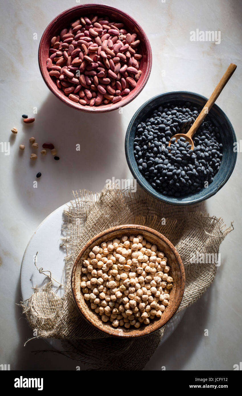 Garbanzo beans/chickpeas,kidney beans/rajma,black beans in individual ceramic bowls on a marble table on top view - Stock Image