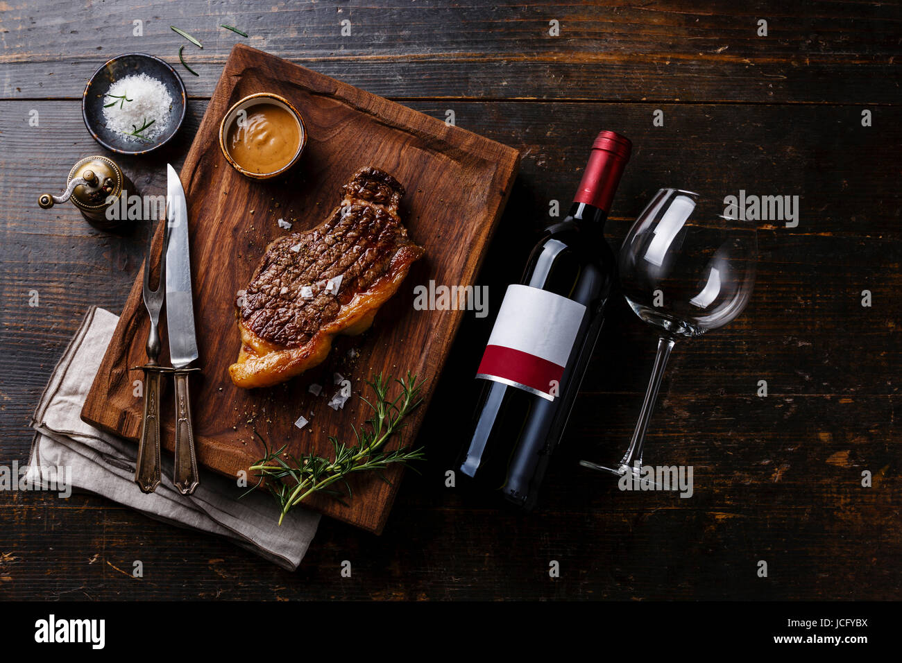 Grilled Steak Striploin with Pepper sauce and bottle of Red wine on wooden background - Stock Image