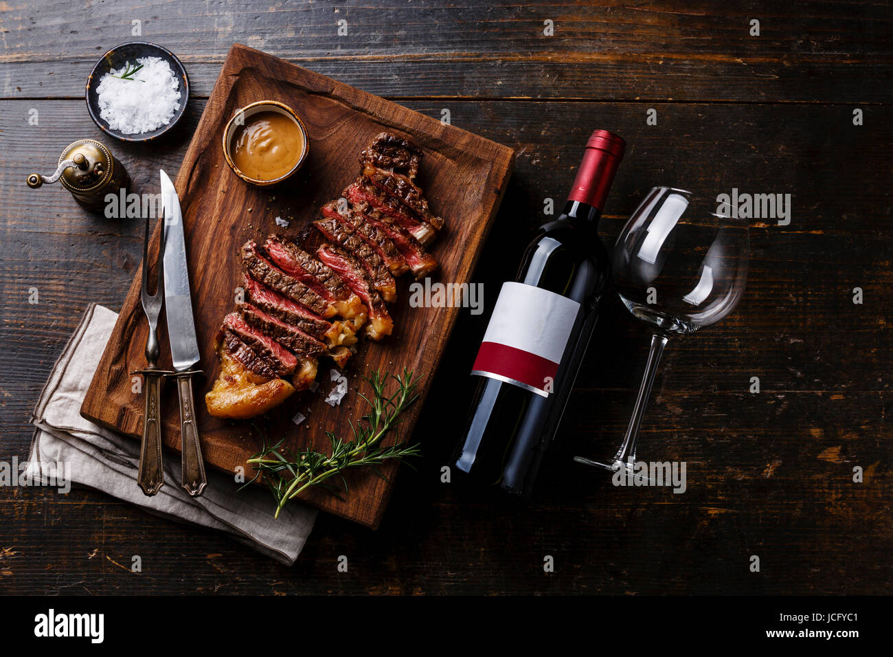 Grilled sliced Steak Striploin with Pepper sauce and bottle of Red wine on wooden background - Stock Image