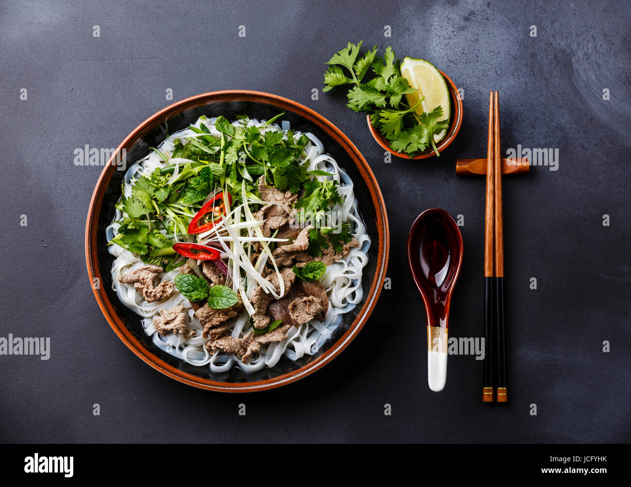 Pho Bo vietnamese Soup with beef on dark background - Stock Image