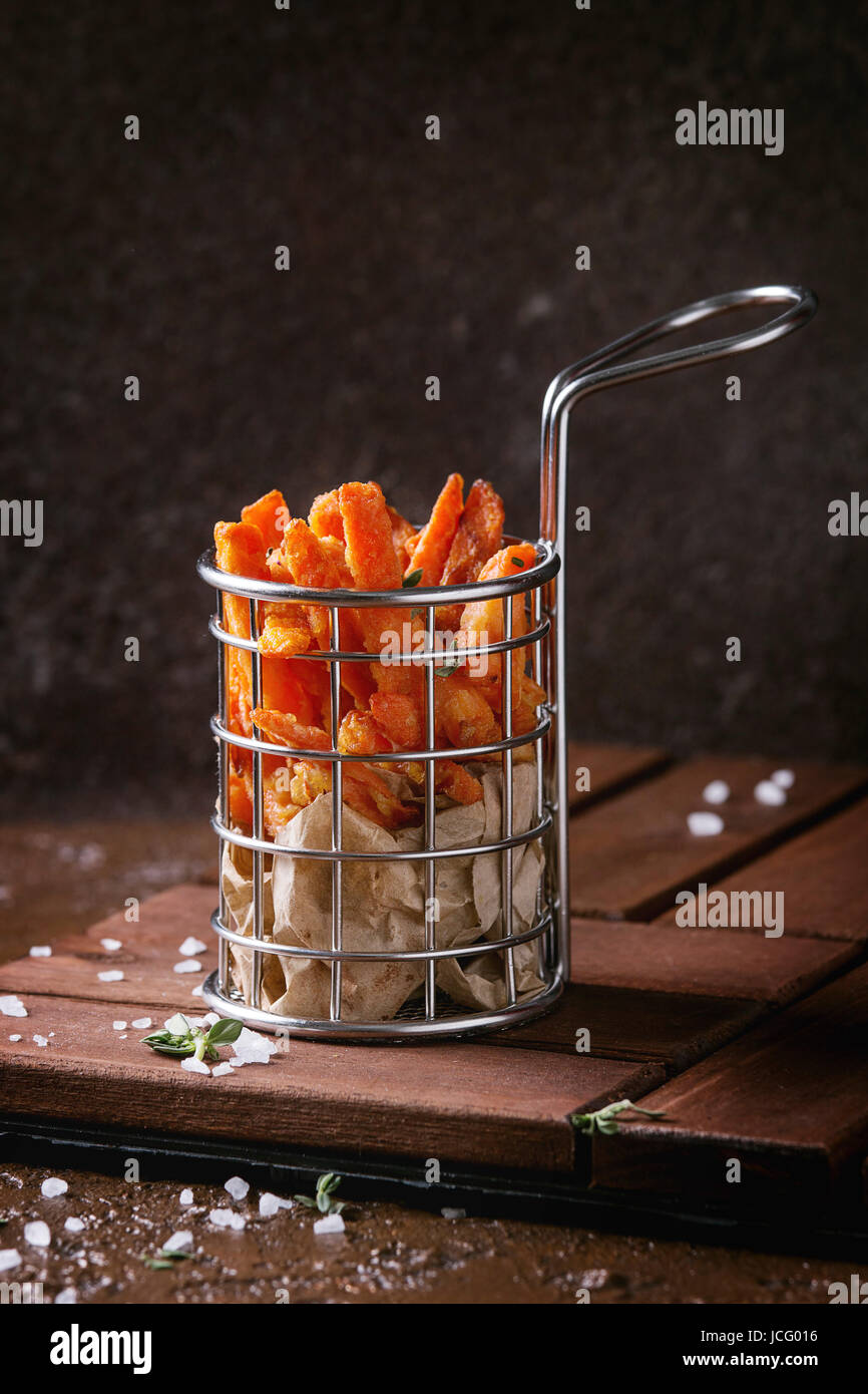 Seet potato or carrot french fries served in frying basket with salt, thyme on wooden board over brown texture background. - Stock Image