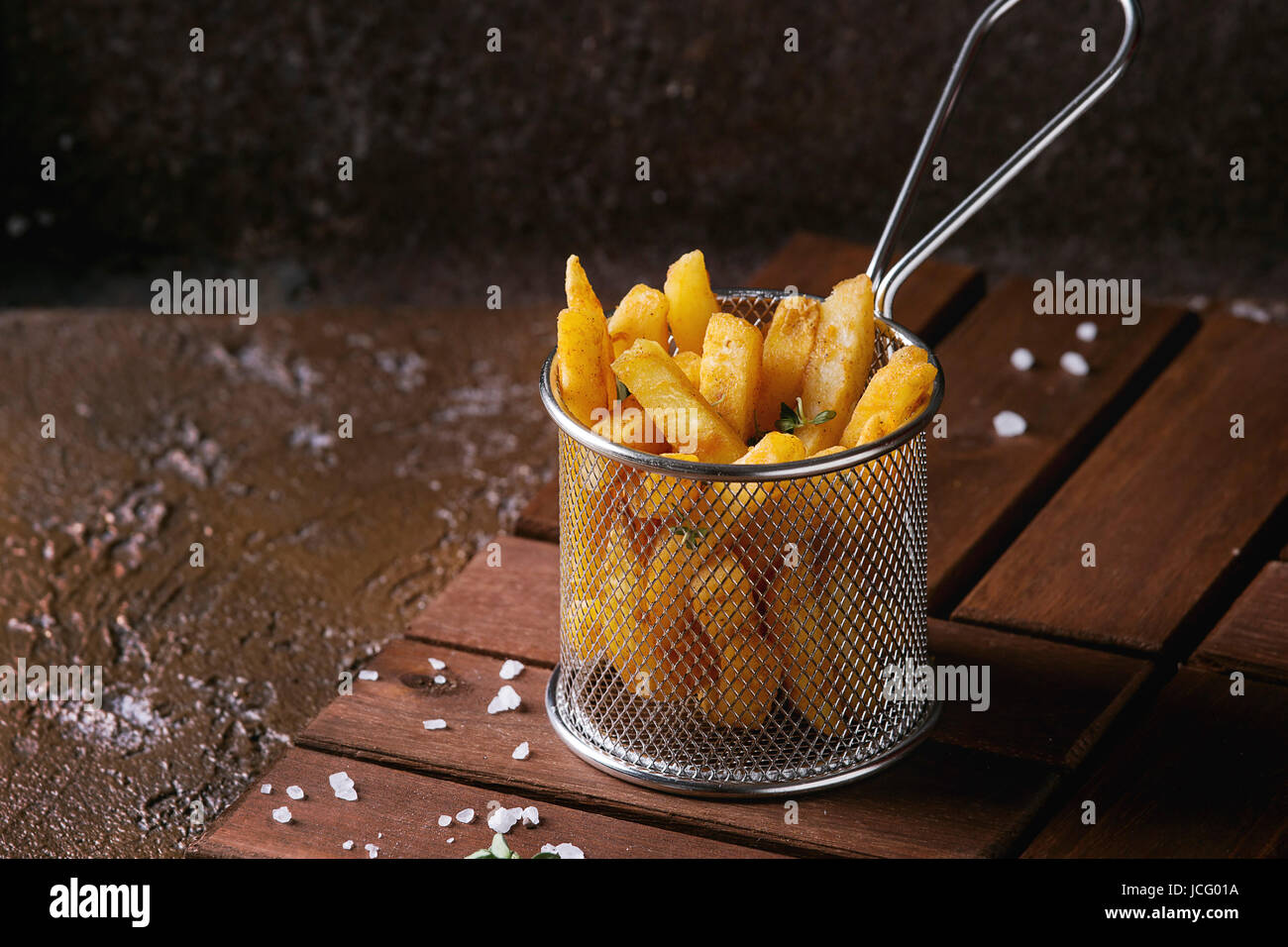 Traditional french fries potatoes served in frying basket with salt, thyme on wooden board over brown texture background. - Stock Image