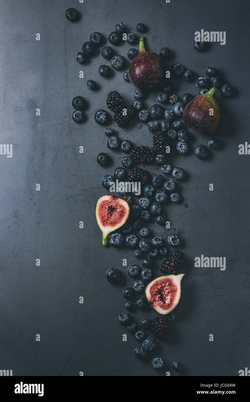Variety of fresh berries blueberry, dewberry and figs over dark metal background. Top view with space. Toned image - Stock Image