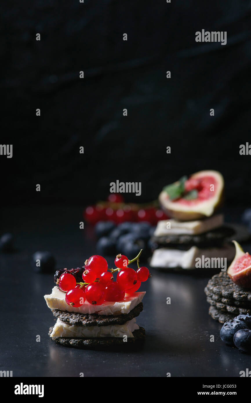 Black charcoal crackers with camembert brie cheese and berries blueberry, dewberry, red currant and sliced figs, - Stock Image
