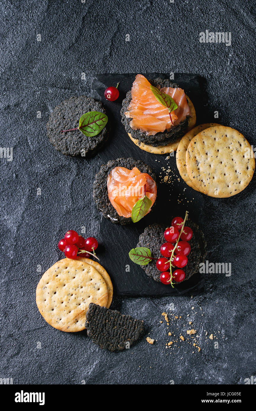 Stack of black wholegrain charcoal and traditional crackers with smoked salmon, cream cheese, green salad and red Stock Photo