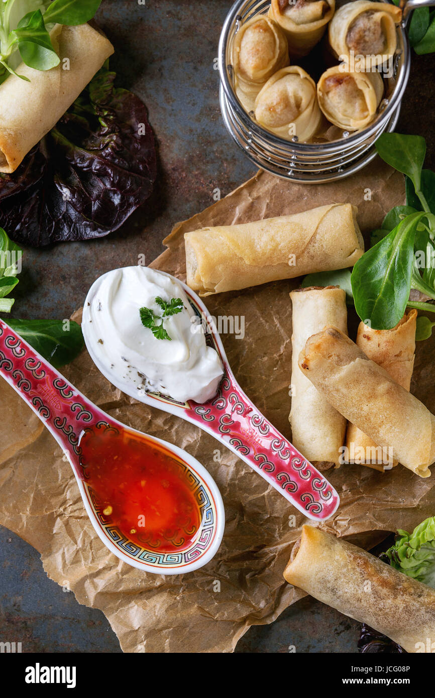 Fried spring rolls with red and white sauces in china spoons, served on crumpled paper and in fry basket with green - Stock Image