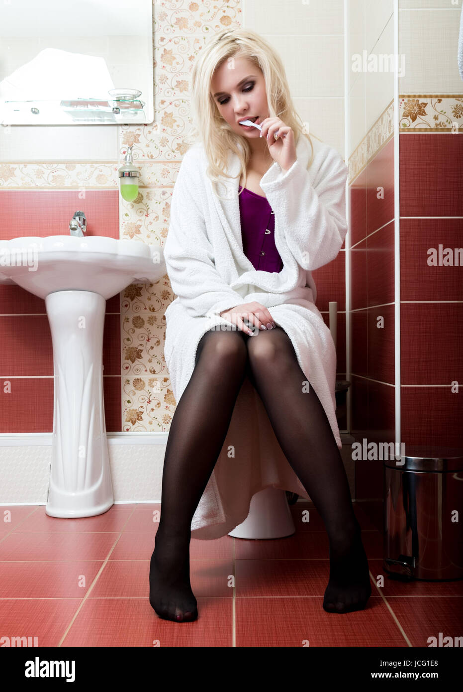 Young woman cleaning her teeth sitting on the toilet in a bathroom Stock Photo