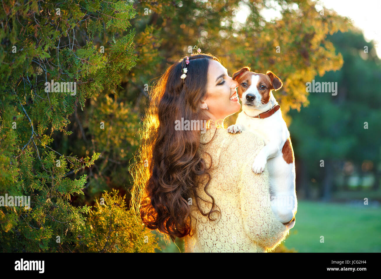 Beautiful woman playing with her dog Jack Russell Terrier. Outdoor portrait. series - Stock Image