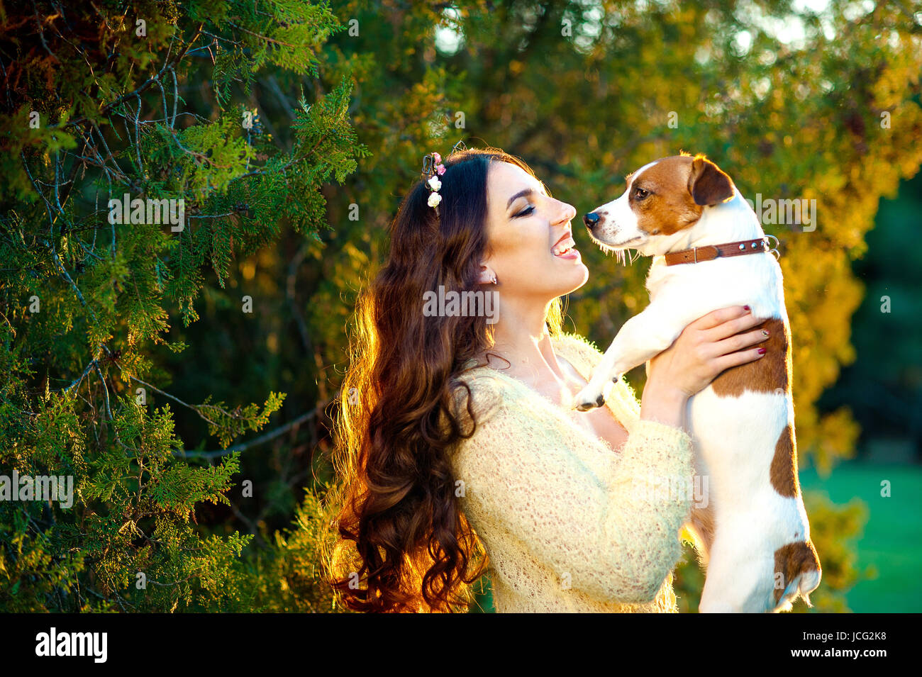 Happy young woman hugging and having fun with her Jack Russell Terrier outdoors - Stock Image
