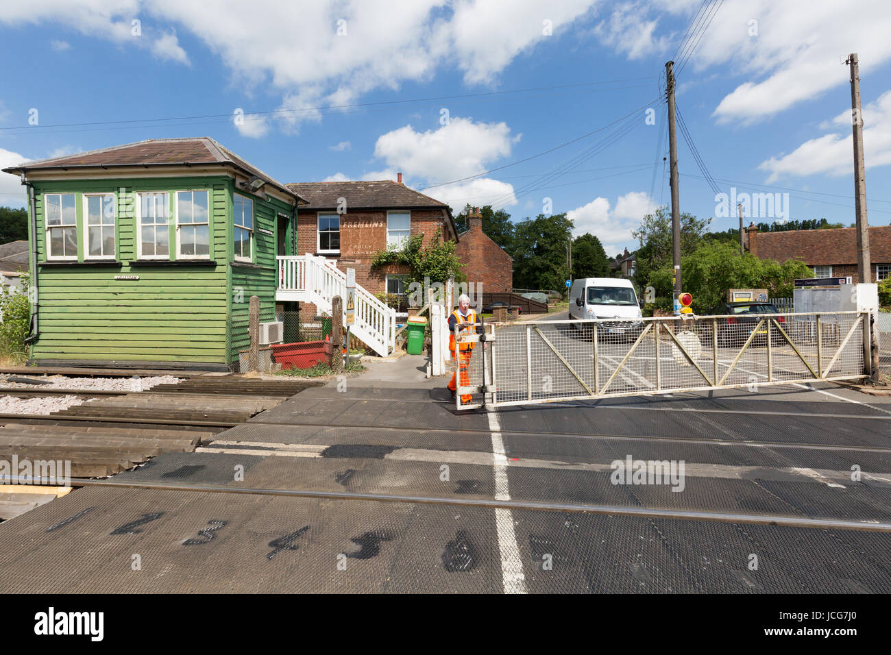 Railway worker opening the gates at a Manual level crossing, Chartham, Kent England UK - Stock Image