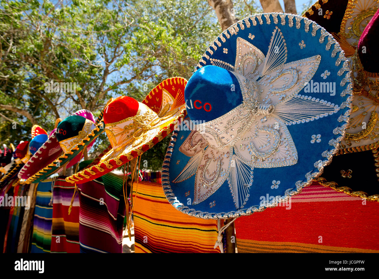 colorful Mexican sombreros and ponchos lined up outdoors - Stock Image