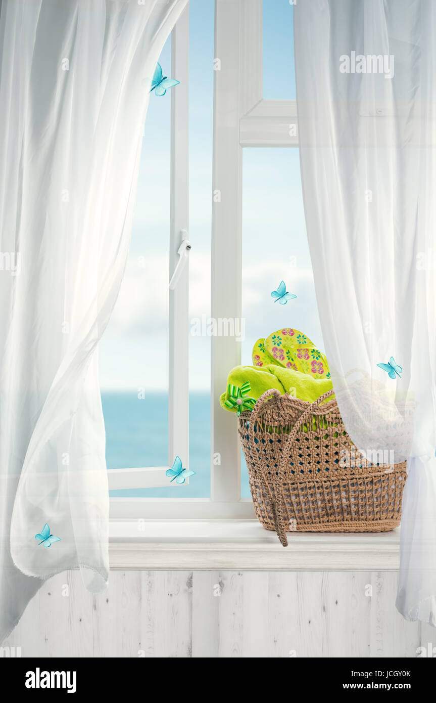 Beach basket filled with towels and flip flops with open window and billowing net curtains - Stock Image
