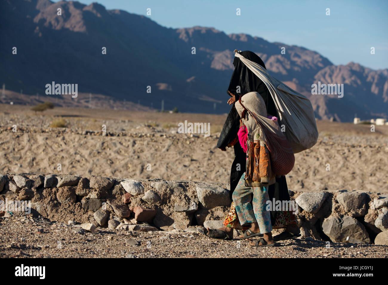 Bedouin woman walking with her kid. Nuweiba. Egypt - Stock Image