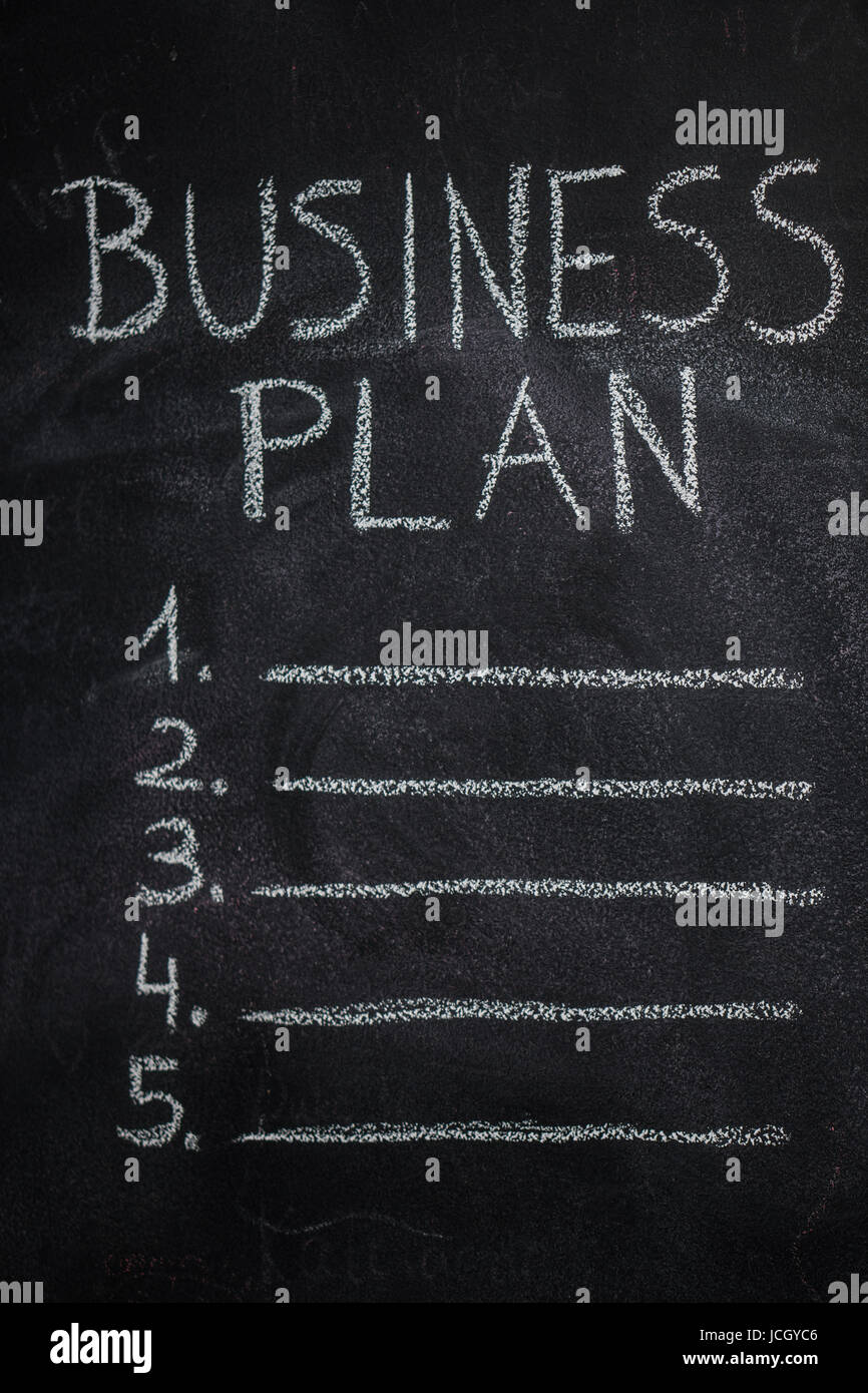 Business plan list written with white chalk on blackboard. To do list concept - Stock Image