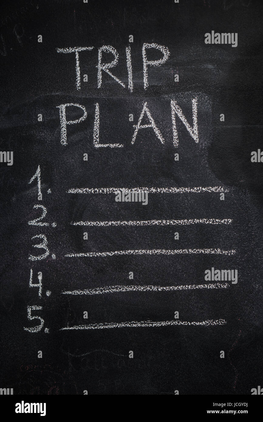 Trip plan list written with white chalk on blackboard. To do list, trip, vacation concept - Stock Image