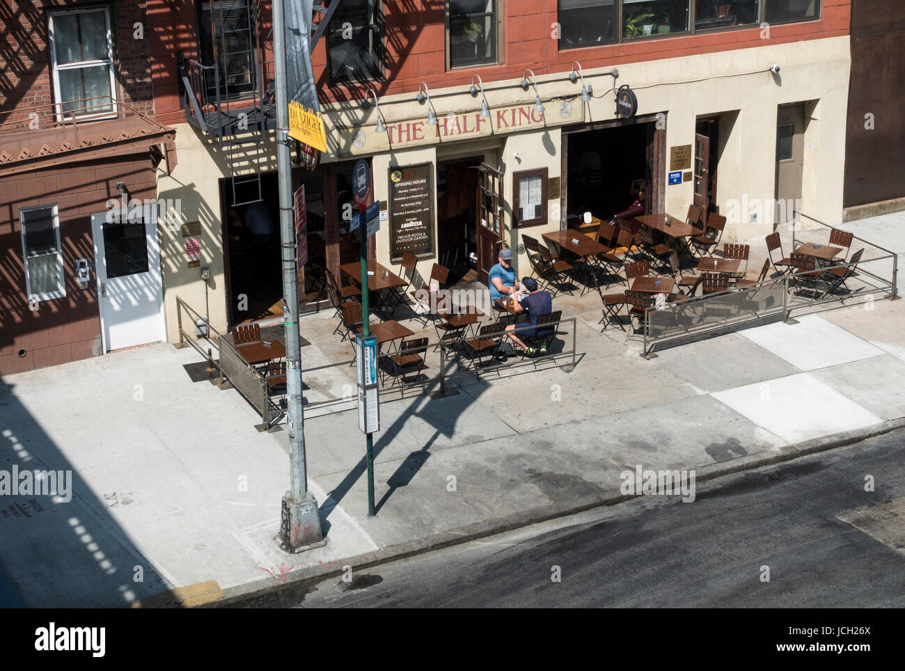 Two men at a table outside The Half King, one of New York's writers bar - Stock Image