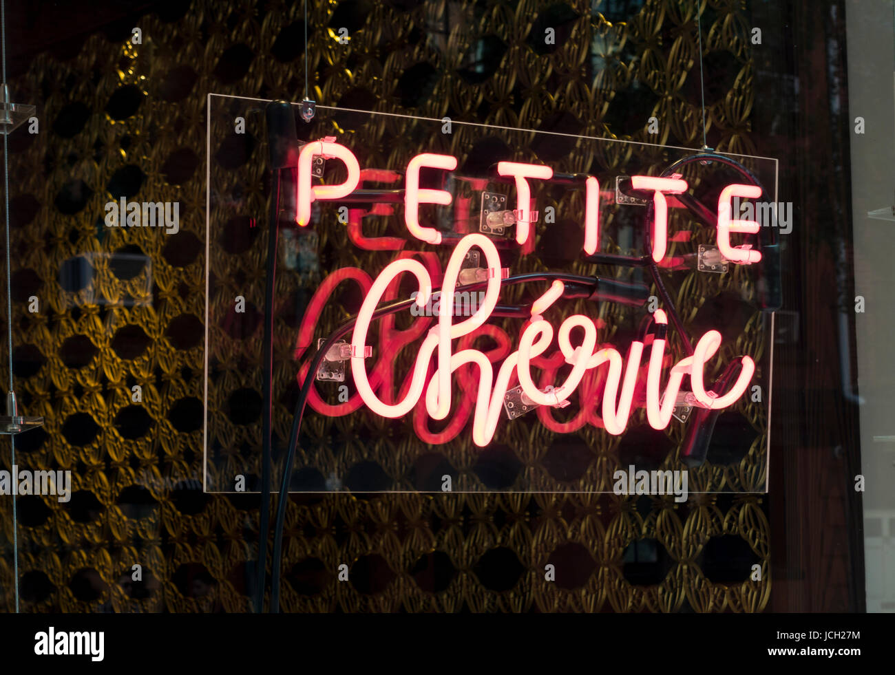 Neon sign in the window of Petite Chérie, a boutique selling perfume - Stock Image