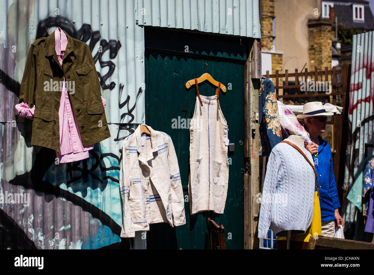 Vintage and secondhand clothes and objects jostle for space athe Columbia Road Flower Market, London - Stock Image