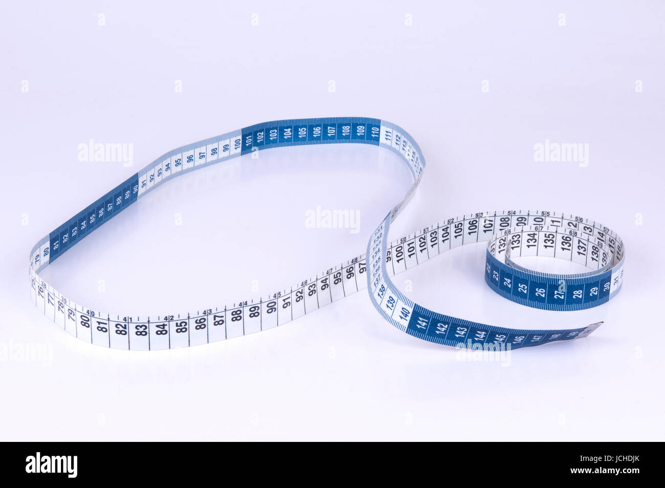 A tape measure or measuring tape is a flexible ruler on white background - Stock Image