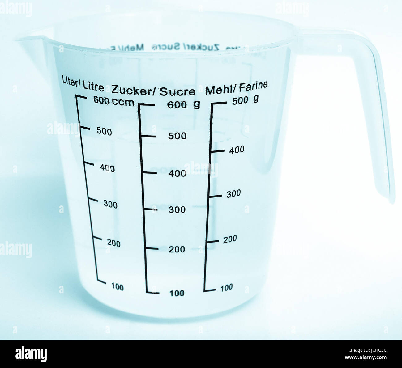 Measuring cup with metric scales for water, sugar and flour - cool cyanotype - Stock Image