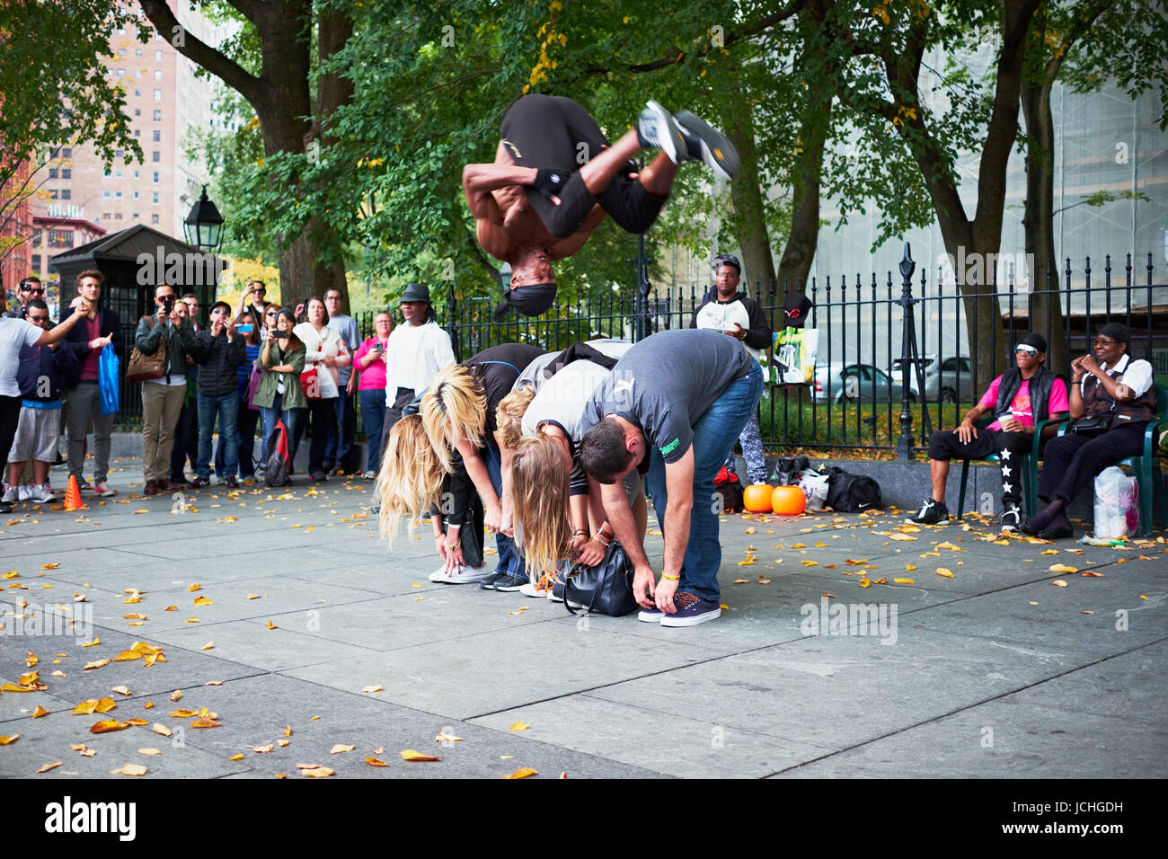 NEW YORK CITY - OCTOBER 18, 2014: a man from a perfomance group is doing a somersault over a line of tourists on - Stock Image