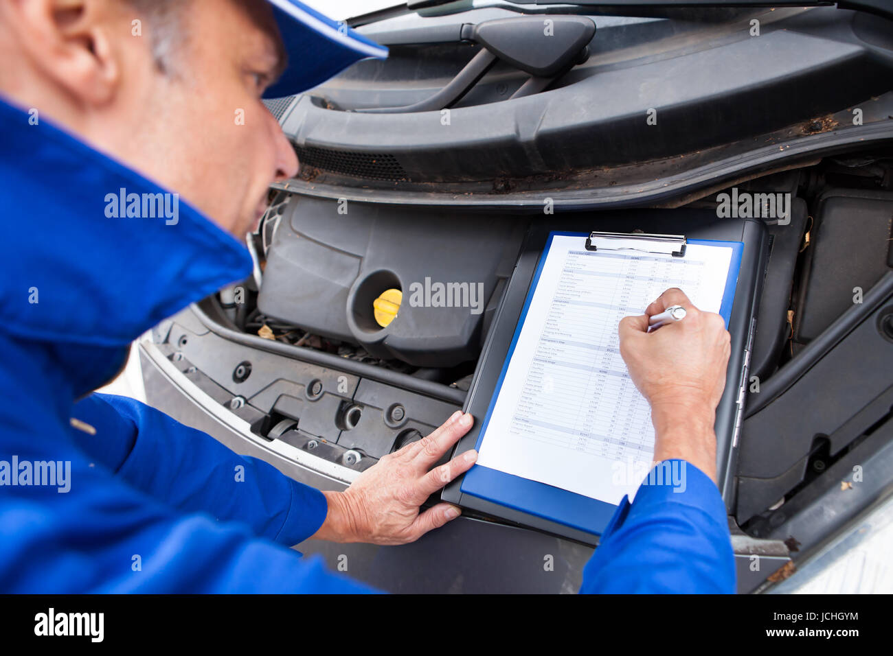 close up of a mature mechanic maintaining car records stock photo