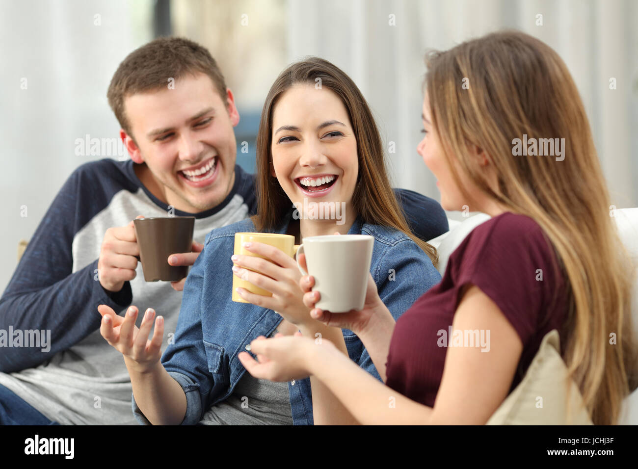 Three happy friends talking and laughing loud holding drinks sitting on a sofa in the living room at home - Stock Image