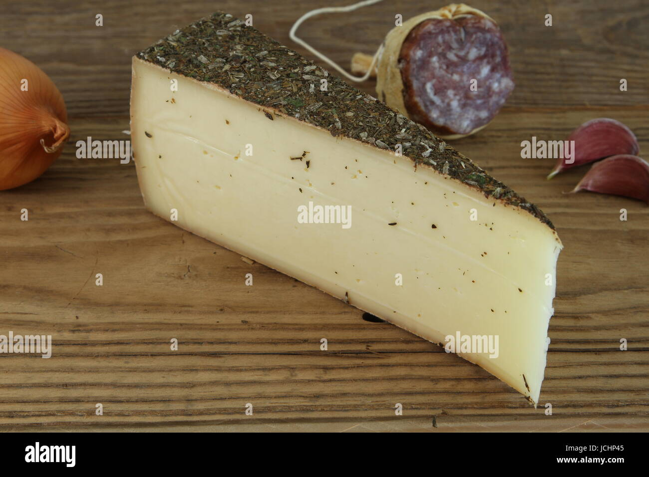 Traditional Swiss Cheese with onion, garlic and Salami on wooden table, Close up - Stock Image